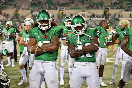 North Texas Mean Green defensive tackle Ulaiasi Tauaalo (15) and North Texas Mean Green running back Andrew Tucker (25) celebrate after wining an NCAA Football game between the Lamar Cardinals and the North Texas Mean-Green Eagles at Apogee Stadium in Denton, Texas