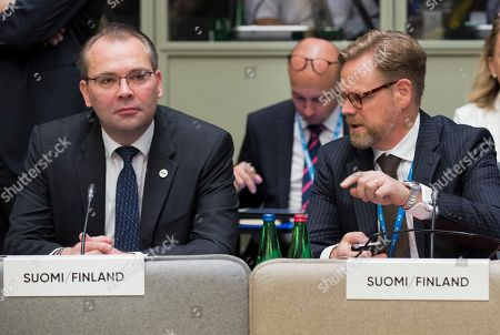 Finland's Defence Minister Jussi Niinisto, left, listens to his unidentified colleague at the beginning of the informal meeting of the EU ministers of defence in Tallinn, Estonia