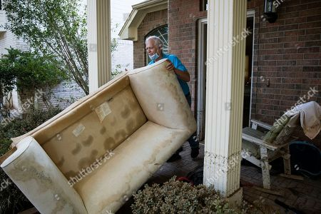 Steve Thompson pushes a flood damaged couch out of his house in the aftermath of Hurricane Harvey, at the Canyon Gate community in Katy, Texas