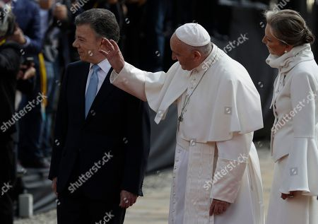 Pope Francis waves as he arrives with Colombia's President Juan Manuel Santos and first lady Maria Clemencia Rodriguez Munera to the presidential palace in Bogota, Colombia,. Pope Francis opens the first full day of his Colombia visit on Thursday