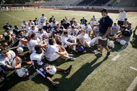 Coach Barry Campbell speaks with the Kingwood High School football team at the end of practice, at Turner Stadium in Humble, Texas. Damage from Hurricane Harvey to their school forced the Kingwood team to practice 9 miles away at another high school and its students will attend classes at still another school in the days to come