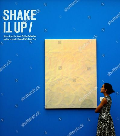 Stock Image of A Sotheby's employee looks at the untitled acrylic on canvas picture by Tauba Auerbach with the estimated value of 600,000-800,000 pounds, 675,000-900,000 euro, at the Sotheby's auction house in London, . Over 300 works from Mario Testino's Remarkable Personal Art Collection are on display for the first time at Sotheby's in London From Sept. 8 -13