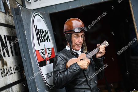 Graeme Hardy dressed as George Formby poses for a photo at the annual Goodwood Revival historic motor racing festival, celebrating mid-20th century motorsport.