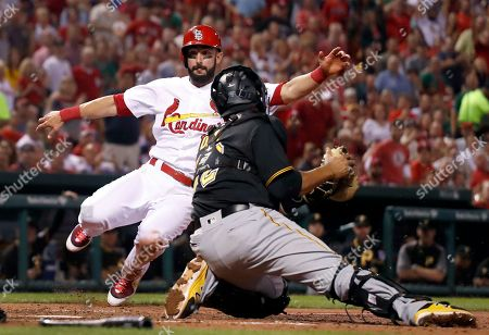 St. Louis Cardinals' Matt Carpenter, left, scores past Pittsburgh Pirates catcher Elias Diaz during the fifth inning of a baseball game, in St. Louis
