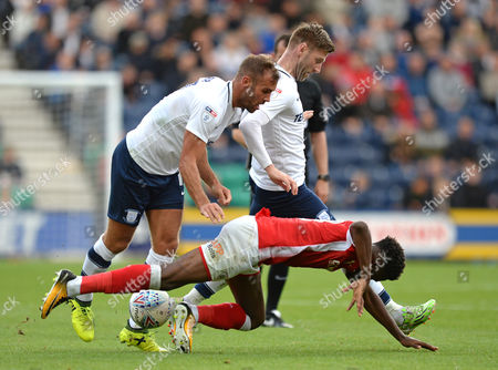 Stock Picture of Ike Ugbo of Barnsley (right) falls to the ground after being challenged by Tommy Spurr of Preston North End (left) and Paul Gallagher of Preston North End