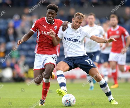 Tommy Spurr of Preston North End (right) fends off Ike Ugbo of Barnsley