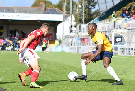 Chinua Cole of Torquay United battles for the ball with Paul Rutherford of Wrexham, during the Vanarama National League match between Torquay United and Wrexham at Plainmoor, Torquay, Devon on September 09