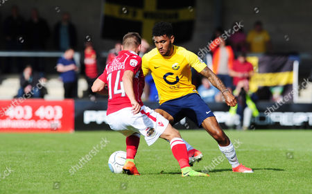 Jamie Reid of Torquay United battles for the ball with Paul Rutherford of Wrexham, during the Vanarama National League match between Torquay United and Wrexham at Plainmoor, Torquay, Devon on September 09