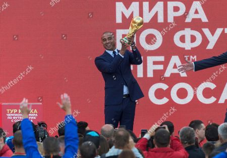 Former French soccer star David Trezeguet raises up the FIFA World Cup trophy during its presentation at Moscow's Luzhniki Stadium, Russia, on . From September 2017, the original trophy starts its tour over 24 Russian cities and more than 50 countries around the globe ahead of 2018 World Cup to start at Luzhniki stadium on June 14, 2018