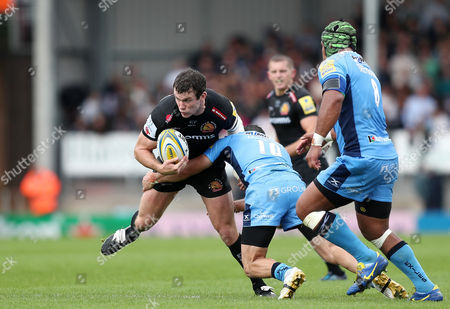 Ian Whitten of Exeter Chiefs is tackled by James Marshall of London Irish