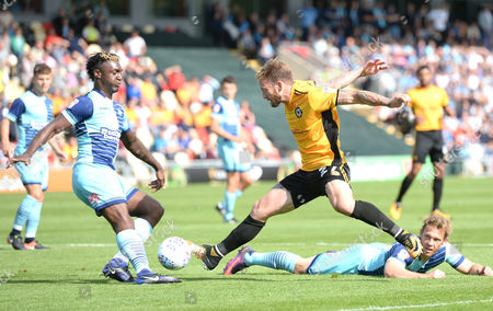 Sean Rigg of Newport County is tackled by Anthony Stewart of Wycombe Wanderers.