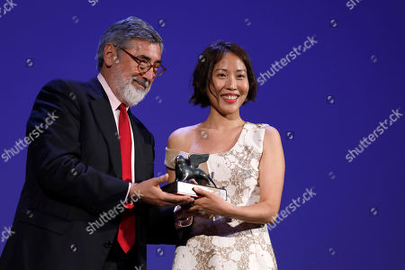 Gina Kim, John Landis. Gina Kim, right, is awarded the Venice Virtual Reality Prize for best VR story from director John Landis at the 74th Venice Film Festival at the Venice Lido, Italy