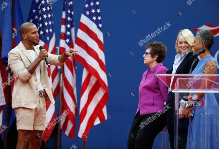 Sydney James Harcourt, left, motions to Billie Jean King, Emma Stone and Katrina Adams as he sings during the opening ceremony for the women's singles championship match of the U.S. Open tennis tournament, in New York