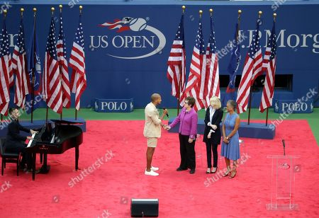 Sydney James Harcourt, left, sings to Billie Jean King, Emma Stone and Katrina Adams as he sings during the opening ceremony for the women's singles championship match of the U.S. Open tennis tournament, in New York