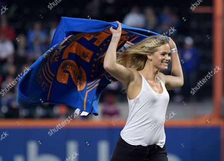 Stock Image of Model Erin Heatherton comes off the mound after throwing out the first pitch before a baseball game between the Cincinnati Reds and the New York Mets, in New York