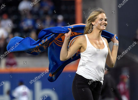 Model Erin Heatherton comes off the mound after throwing out the first pitch before a baseball game between the Cincinnati Reds and the New York Mets, in New York