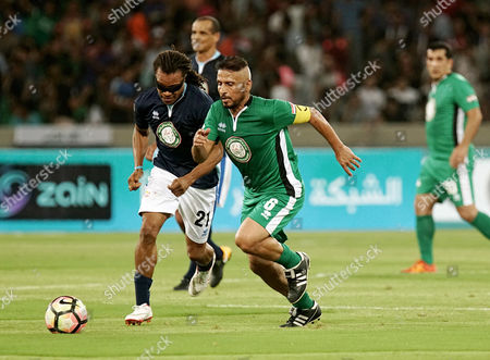Iraq Stars' Habeeb Jaafer, front right, vies for the ball with World Stars' Edgar Davids during their friendly soccer match in Basra, southeast of Baghdad, Iraq