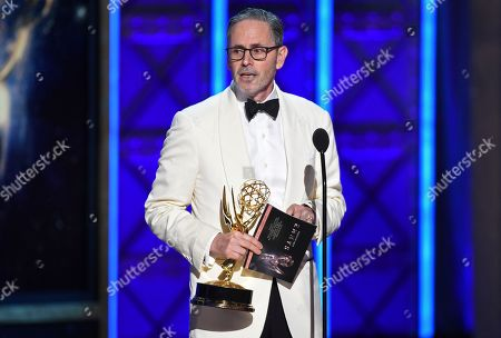 """Keith Ian Raywood accepts the award for outstanding production design for a variety nonfiction reality or reality competition for """"Saturday Night Live"""" during night one of the Television Academy's 2017 Creative Arts Emmy Awards at the Microsoft Theater, in Los Angeles"""