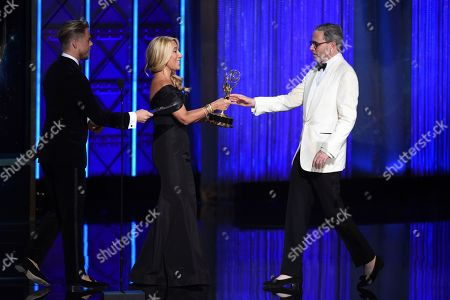 """Derek Hough, Lori Grenier, Keith Ian Raywood. Derek Hough, left, and Lori Grenier present the award for outstanding production design for a variety nonfiction reality or reality competition to Keith Ian Raywood for """"Saturday Night Live"""" during night one of the Television Academy's 2017 Creative Arts Emmy Awards at the Microsoft Theater, in Los Angeles"""