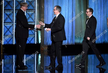 """T Bone Burnett, Jon Michaels, Cameron Frankley. EXCLUSIVE - T Bone Burnett, left, presents the award for outstanding sound editing for a nonfiction program (single or multi camera) for """"The Beatles: Eight Days A Week - The Touring Years"""" to Jon Michaels, center, and Cameron Frankley, right, during night one of the Television Academy's 2017 Creative Arts Emmy Awards at the Microsoft Theater, in Los Angeles"""