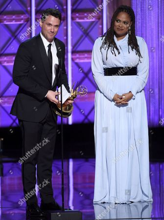 """Spencer Averick, Ava DuVernay. Spencer Averick, left, and Ava DuVernay accept the award for outstanding writing for a nonfiction program for """"13th"""" during night one of the Television Academy's 2017 Creative Arts Emmy Awards at the Microsoft Theater, in Los Angeles"""
