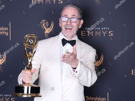 Keith Ian Raywood poses for a portrait with the award for Outstanding Production Design for a Variety, Nonfiction, Reality or Reality-Competition Series for 'Saturday Night Live' during night one of the Television Academy's 2017 Creative Arts Emmy Awards at the Microsoft Theater, in Los Angeles