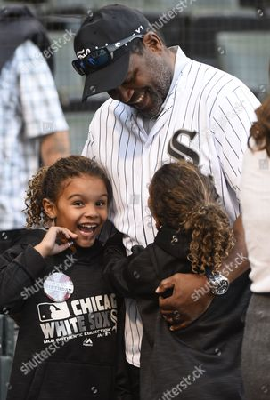 Stock Image of Tim Raines, Ava Raines, Amelie Raines. Hall of Famer and former Chicago White Sox player Tim Raines talks with twin seven-year-old daughters Ava, left, and Amelie Raines before the baseball game between the White Sox and the San Francisco Giants in Chicago on