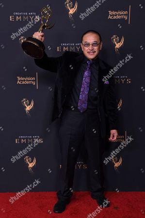 """James Lew poses in the press room with the award for outstanding stunt coordination for a drama series, limited series or movie for """"Luke Cage"""" during night two of the Creative Arts Emmy Awards at the Microsoft Theater, in Los Angeles"""