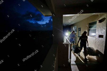 Stock Photo of Joe Raymond, Laura Raymon, Caitlin Raymond. Members of the Raymond family, from left, Joe, Laura and their daughter Caitlin, 12, leave the fourth floor apartment of Joe's mother where they rode out Hurricane Irma to return to their low lying home a mile away in Marco Island, Fla