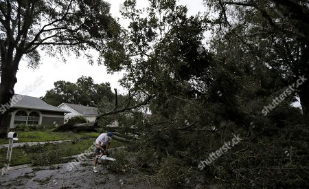 Brian Baker, of Valrico, Fla., cuts an Oak tree that fell across Falling Leaves Drive after Hurricane Irma passed through the area, in Valrico, Fla