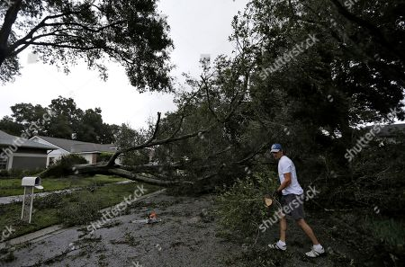 Brian Baker, of Valrico, Fla., cuts up an Oak tree that fell across Falling Leaves Drive after Hurricane Irma passed through the area, in Valrico, Fla