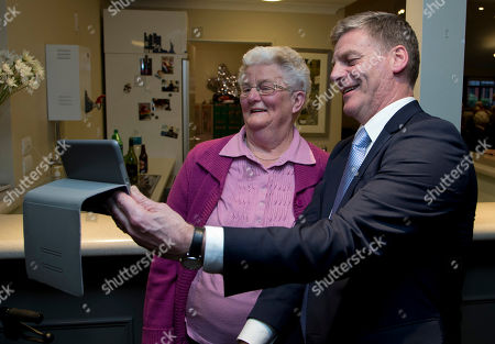 New Zealand Prime Minister Bill English, right, takes a selfie with a resident during a visit to a retirement village in Christchurch, New Zealand, . Advance voting began Monday, Sept. 11, 2017, for New Zealand's general election, which could see a change of government in the South Pacific nation for the first time in nine years
