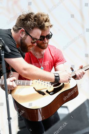 Zach Swon, left, and Colton Swon, right, of The Swon Brothers sign a guitar to be given away at Riverfront Stage at the CMA Music Festival, in Nashville, Tenn