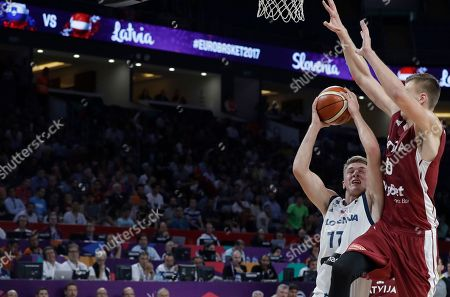 Slovenia's Luka Doncic, left, jumps to score a basket as Latvia's Kristaps Porzingis tries to stop him during their Eurobasket European Basketball Championship quarterfinal match in Istanbul, Tuesday, Sept. 12. 2017