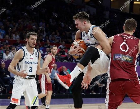 Slovenia's Luka Doncic, center, battles for the ball with Latvia's Kristaps Porzingis during their Eurobasket European Basketball Championship quarterfinal match in Istanbul, Tuesday, Sept. 12. 2017