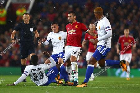 Eder Alvarez Balanta of Basel tackles Henrikh Mkhitaryan of Manchester United