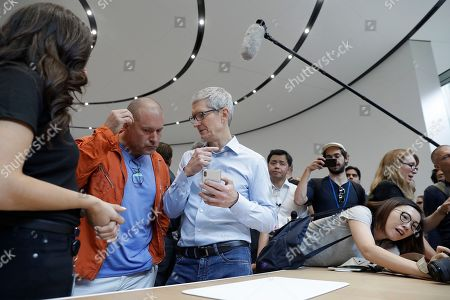 Jonathan Ive, Tim Cook. Apple CEO Tim Cook, center, and Jonathan Ive, second from left, Chief Design Officer shows the new iPhone X in the showroom after the new product announcement at the Steve Jobs Theater on the new Apple campus, in Cupertino, Calif