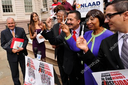 Douglas A. Michels, left, Dayana Mendoza, Robert Jackson, Guillermo Chacon and Dr. Monica Sweeney show how to use the OraQuick In-Home HIV Test on the steps of City Hall on the 10th Annual National Latino HIV/AIDS Awareness Day, in New York