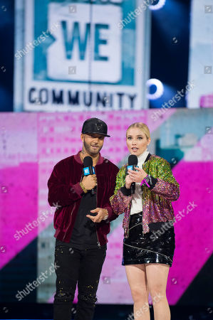Karl Wolf, left, and Liz Trinnear seen on stage at WE Day, in Toronto