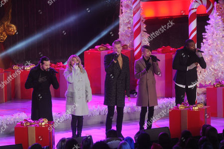 Stock Picture of Pentatonix members Avi Kaplan, Kirstie Maldonado, Scott Hoying, Mitch Grassi, and Kevin Olusola perform during the 83rd Annual Rockefeller Center Christmas Tree Lighting Ceremony, in New York