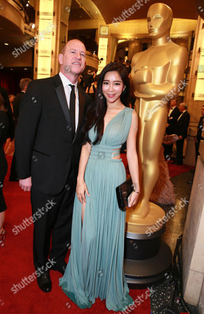 Rob Moore, left, and Betty Zhou arrive at the Oscars, at the Dolby Theatre in Los Angeles