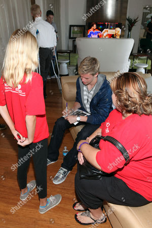 Kenton Duty, center, signs an autograph for CHOC patient Katie Gerberding, 10, at the Xbox 360 and Children's Miracle Network Gaming and Giving for Good (G3) Miracle Lounge on in West Hollywood, Calif