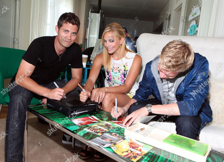 Drew Seeley, Amy Paffrath, center, and Kenton Duty, right, sign autographs at the Xbox 360 and Children's Miracle Network Gaming and Giving for Good (G3) Miracle Lounge on in West Hollywood, Calif