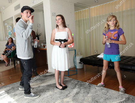 Mitchel Musso, left, plays a game with CHLA patient Eileen Garrido, 13, and CHOC patient Katie Gerberding, 10, at the Xbox 360 and Children's Miracle Network Gaming and Giving for Good (G3) Miracle Lounge on in West Hollywood, Calif
