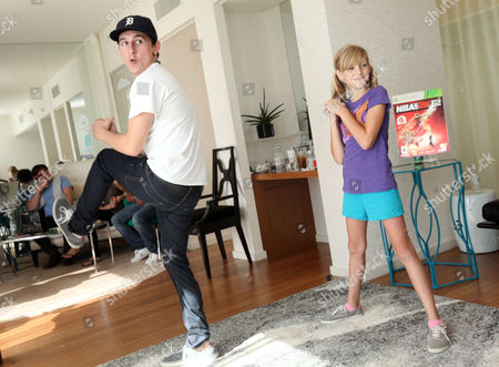 Mitchel Musso, left, plays games with CHOC patient Katie Gerberding, 10, at the Xbox 360 and Children's Miracle Network Gaming and Giving for Good (G3) Miracle Lounge on in West Hollywood, Calif