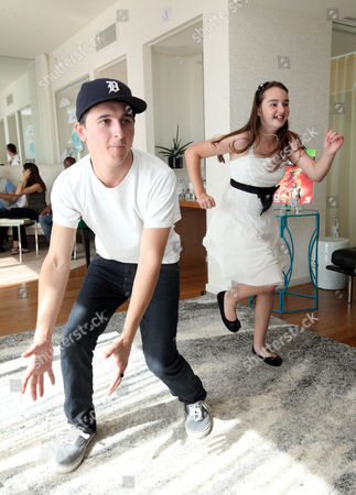 Stock Image of Mitchel Musso, left, plays games with CHLA patient Eileen Garrido, 13, at the Xbox 360 and Children's Miracle Network Gaming and Giving for Good (G3) Miracle Lounge on in West Hollywood, Calif