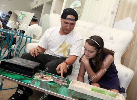 Nick Hogan signs an Xbox at the Xbox 360 and Children's Miracle Network Gaming and Giving for Good (G3) Miracle Lounge as CHLA patient Eileen Garrido, 13, watches on in West Hollywood, Calif
