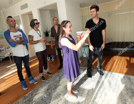 CHLA patient Eileen Garrido, 13, plays a game with, from right, Ryan Good, Evan Ross, Ryan Cabrera and Caleb Garrett at the Xbox 360 and Children's Miracle Network Gaming and Giving for Good (G3) Miracle Lounge on in West Hollywood, Calif