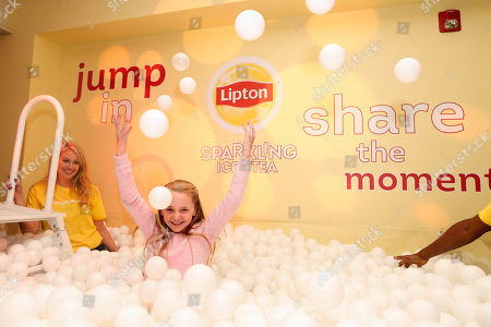 Avery Phillips enjoys the ball pit at the Lipton Sparkling Iced Tea Lounge in Park City, Utah