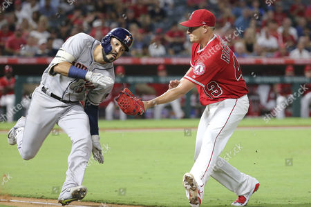 Los Angeles Angels starting pitcher Garrett Richards (43) lags out Houston Astros left fielder Marwin Gonzalez (9) as he tries to avoid the tag and get to first base in the game between the Houston Astros and Los Angeles Angels of Anaheim, Angel Stadium in Anaheim, CA, Photographer: Peter Joneleit